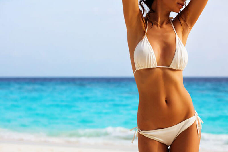 Picture of a smiling woman, happy with her abdomen liposuction she had at Top Plastic Surgeons U.K.  The woman is wearing a white two piece bathing suit and standing on a Costa Rica beach.