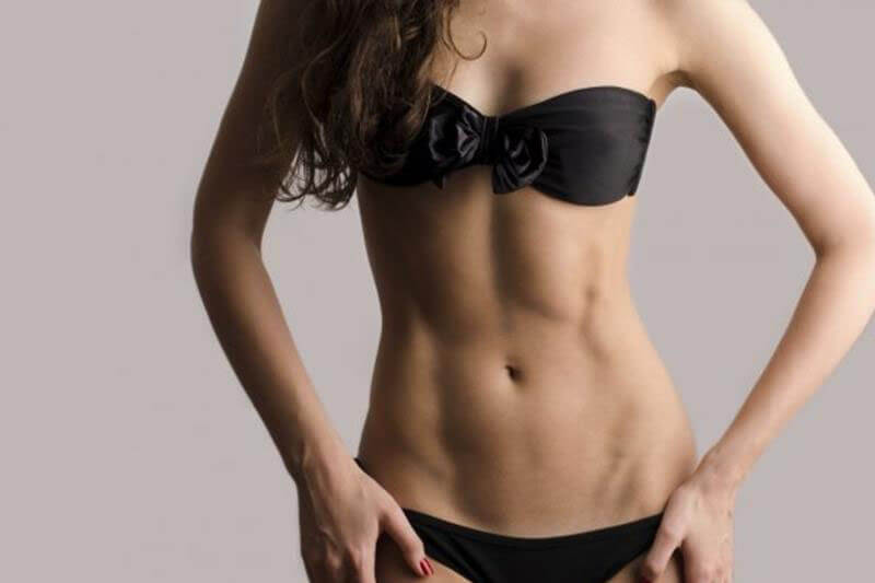 Picture of a woman, happy with her arm lift she had at Top Plastic Surgeons U.K.  The woman is wearing a black two piece bathing suit and standing against a grey background.