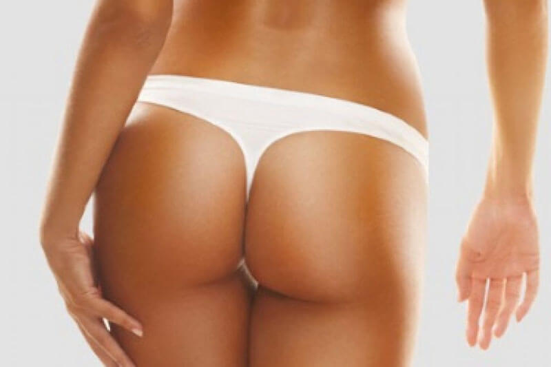 Picture of a tanned woman wearing a white thong, with her back to the camera,  happy with her Brazilian butt lift she had at Top Plastic Surgeons in the U.K.
