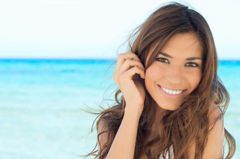Picture of a smiling woman, happy with her eyelid lift she had at Top Plastic Surgeons U.K.  The woman has long brown hair and is standing on a sandy Costa Rican beach with the ocean in the background.