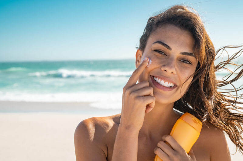 Picture of a smiling woman, happy with her nose surgery she had at Top Plastic Surgeons U.K.  The woman has long brown hair and is standing on a sandy Costa Rican beach with the ocean in the background.