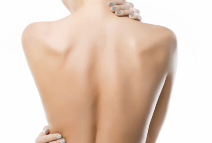 Picture of a woman with her back to the camera and happy with her perfect back liposuction procedure she had at Top Plastic Surgeons in beautiful San Jose, Costa Rica.  She has two hands positioned to highlight the areas of her back liposuction.