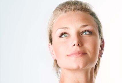 Picture of a woman with blonde hair, facing the camera, and happy with her perfect face lift procedure she had at Top Plastic Surgeons in beautiful San Jose, Costa Rica.  The woman is looking slightly upwards to show her satisfaction with her face lift.