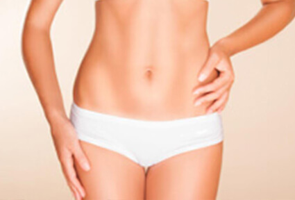 Picture of a trim woman wearing a white bikini bottom, and happy with her perfect tummy tuck she had at Top Plastic Surgeons in beautiful San Jose, Costa Rica.  The woman is facing the camera with both arms down to her sides.