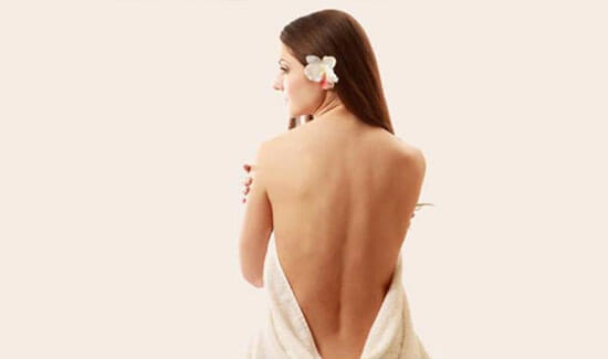 Picture of a woman sitting with her back to the camera and happy with her perfect back liposuction procedure she had at Top Plastic Surgeons in beautiful San Jose, Costa Rica.  The woman has a white towel draped around her.