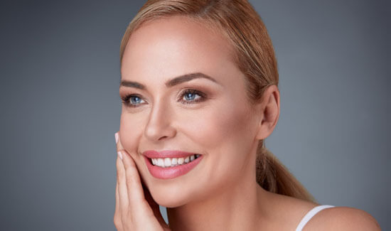 Picture of a smiling woman, facing slightly to the side of the camera and happy with her perfect face lift procedure she had at Top Plastic Surgeons in beautiful San Jose, Costa Rica.  The woman has her hand to the side of her face indicating her happiness with the face lift.