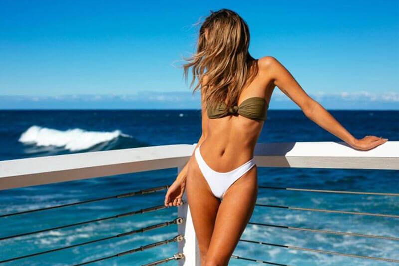 Picture of a smiling woman, happy with her thigh lift she had at Top Plastic Surgeons U.K.  The woman is wearing a white two piece bathing suit and standing against a white railing on a Costa Rica beach.