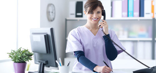 Picture of a receptionist representing Top Plastic Surgeons in San José, Costa Rica.  The woman has short brown hair, is wearing a hospital smock and is standing at the receptionist desk while smiling at the camera.