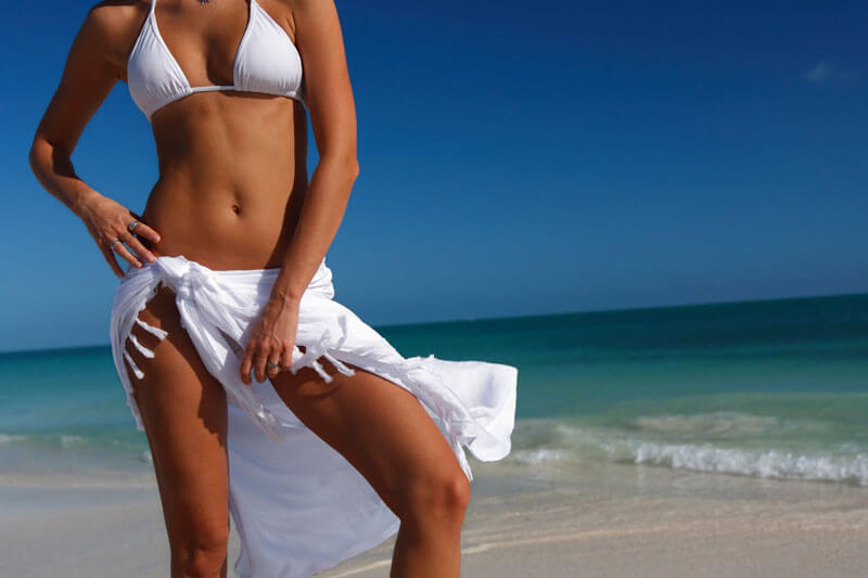 Picture of a smiling woman, happy with her tummy tuck at Top Plastic Surgeons in the U.K.  The woman is wearing a white two piece bathing suit and standing on a Costa Rica beach.